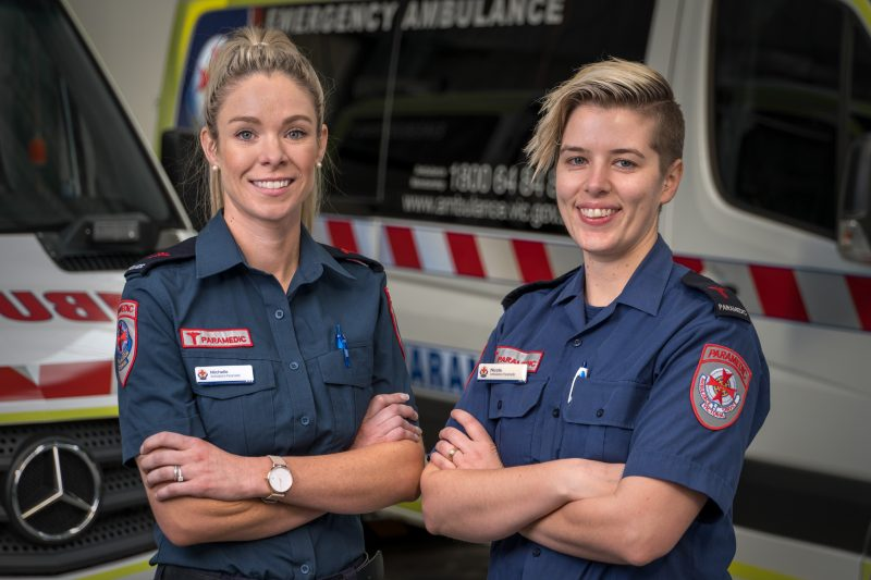 Two female paramedics smiling at camera with ambulances in the background