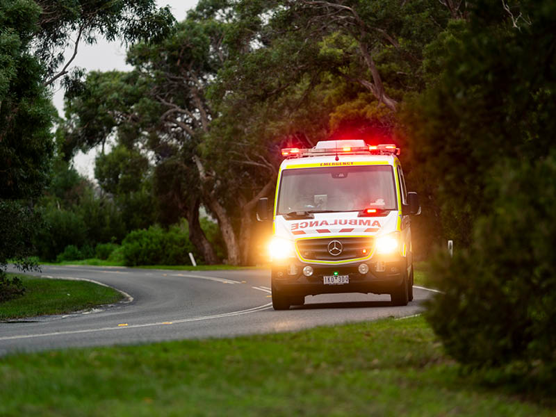 Photograph of ambulance driving on a winding road with it's lights on